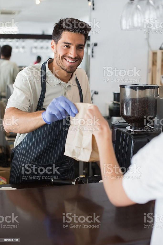 Smiling male barista handing a brown paper bag to a customer stock photo