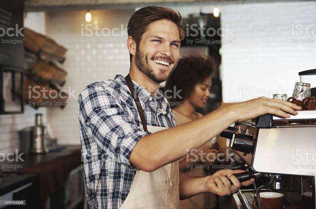 Smiling male barista preparing coffee stock photo