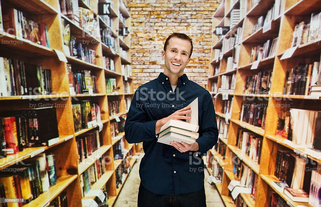 Smiling male bookseller holding books in library stock photo