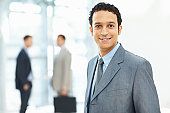 Smiling male business executive with colleagues at back