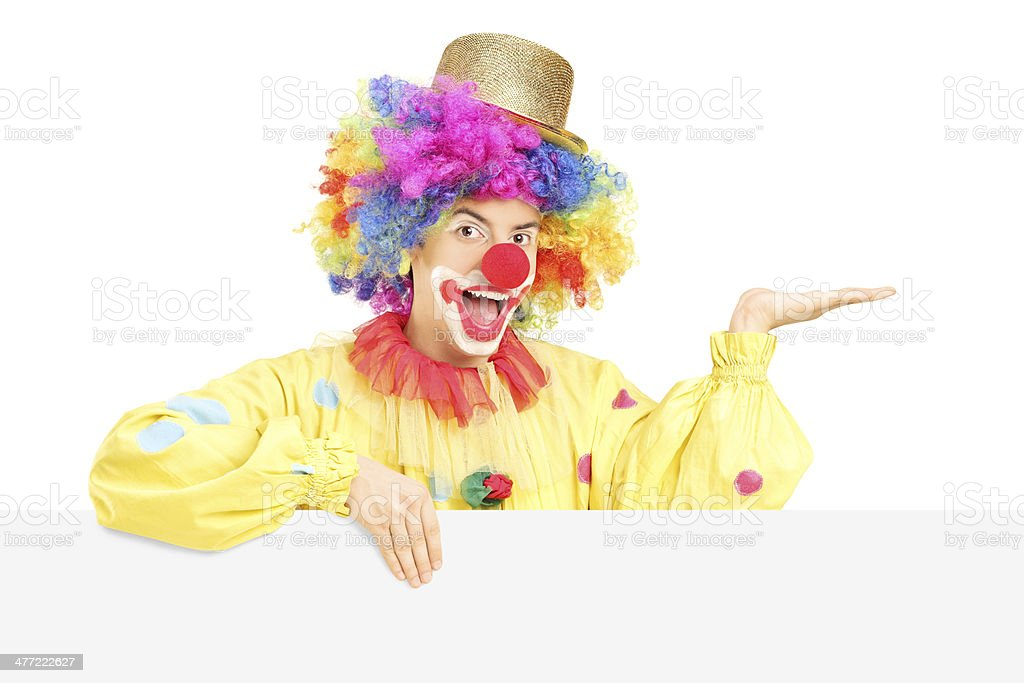 Smiling male clown standing behind blank panel gesturing with hand royalty-free stock photo