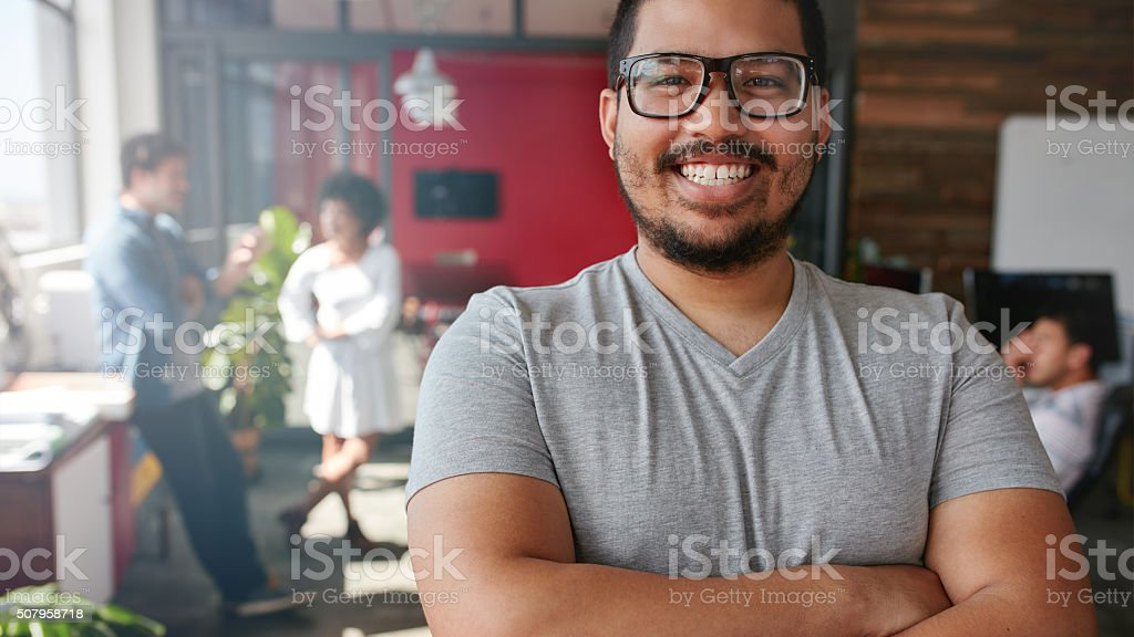 Smiling male designer looking at camera at office stock photo