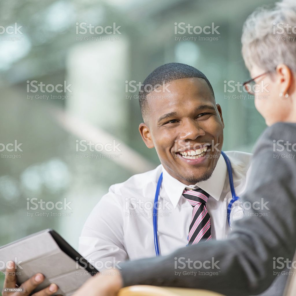 Smiling Male Doctor Discussing Test Results with Senior Patient in Office royalty-free stock photo