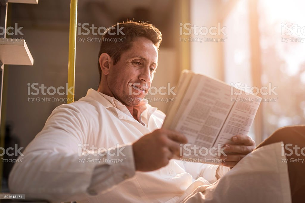 Smiling male doctor relaxing while reading a book. stock photo