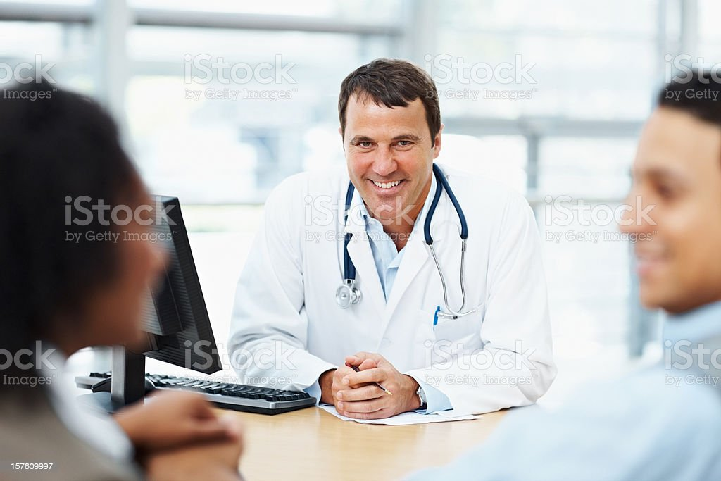 Smiling male doctor speaking to a patient royalty-free stock photo