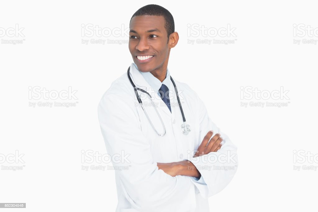 Smiling male doctor standing with arms crossed stock photo