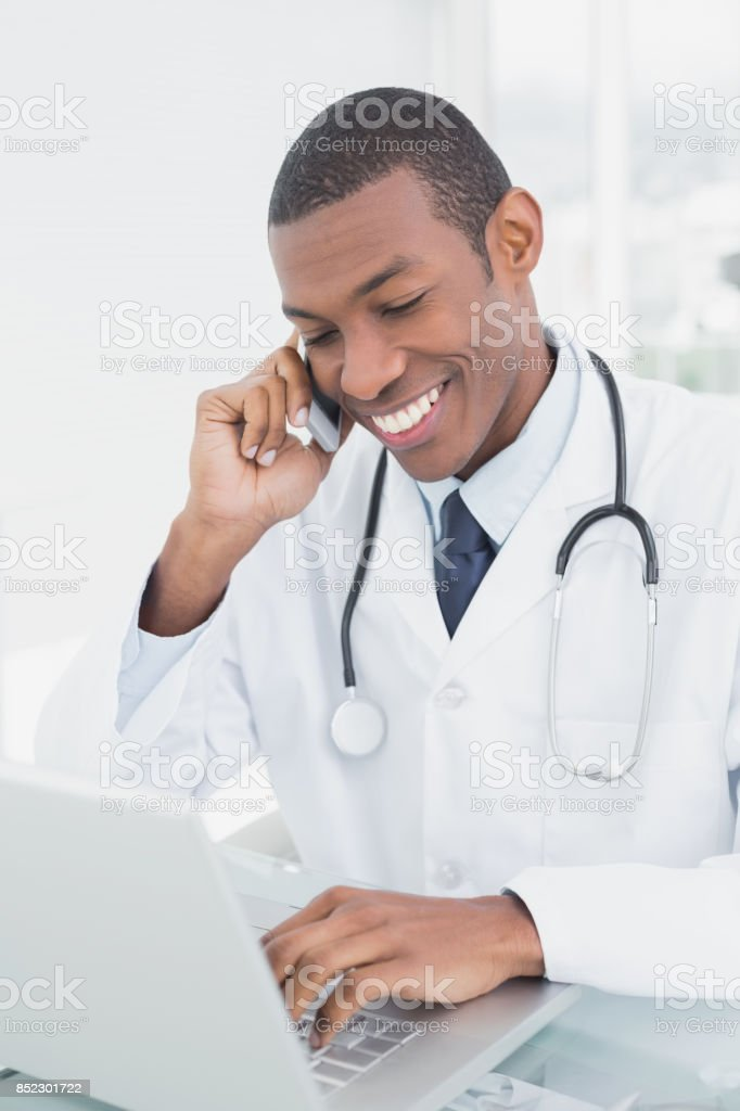 Smiling male doctor using cellphone and laptop stock photo