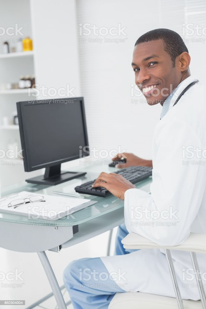 Smiling male doctor using computer at medical office stock photo