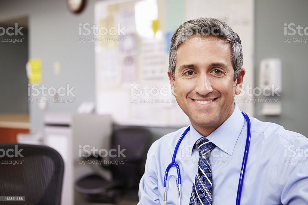Smiling male doctor with blue stethoscope at nurse's station stock photo