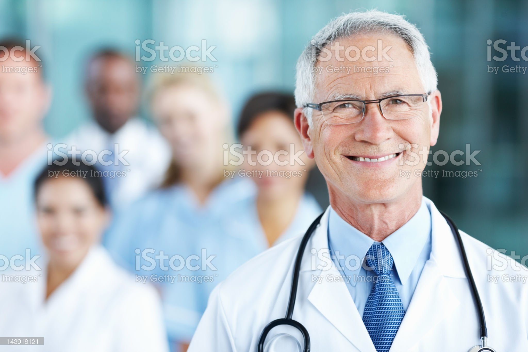 Smiling, male doctor with confident team royalty-free stock photo