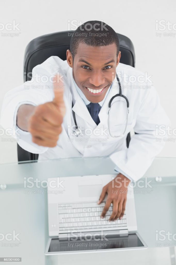 Smiling male doctor with laptop gesturing thumbs up stock photo