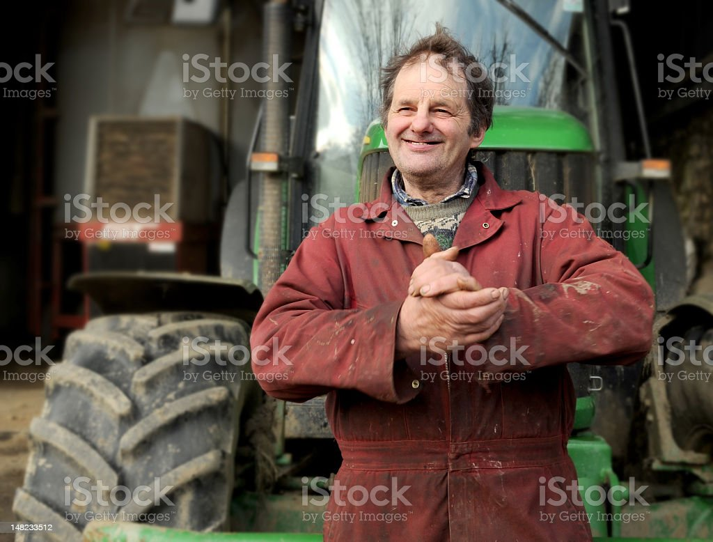 A smiling male farmer in red overalls with his hands clasped royalty-free stock photo