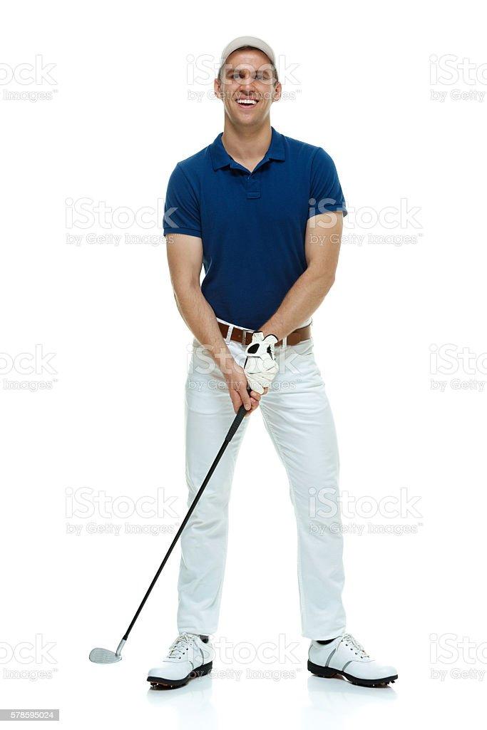 Smiling male golfer swinging stock photo