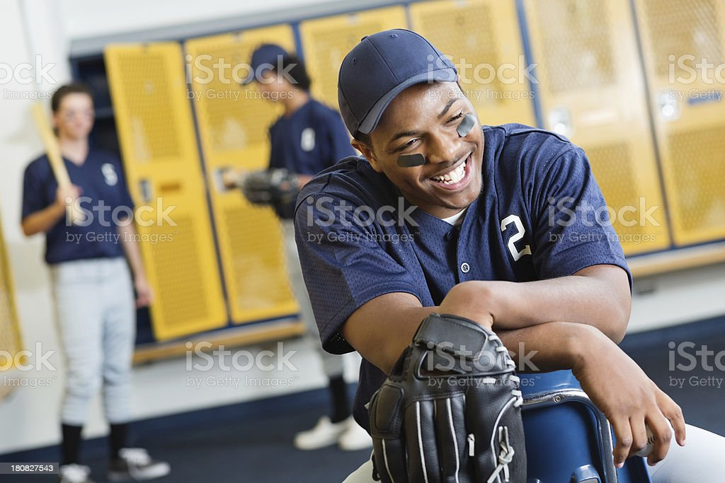 Smiling male high school baseball player in locker room. royalty-free stock photo