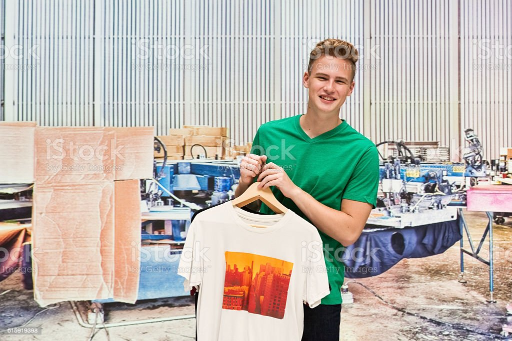 Smiling male holding t-shirt in warehouse stock photo