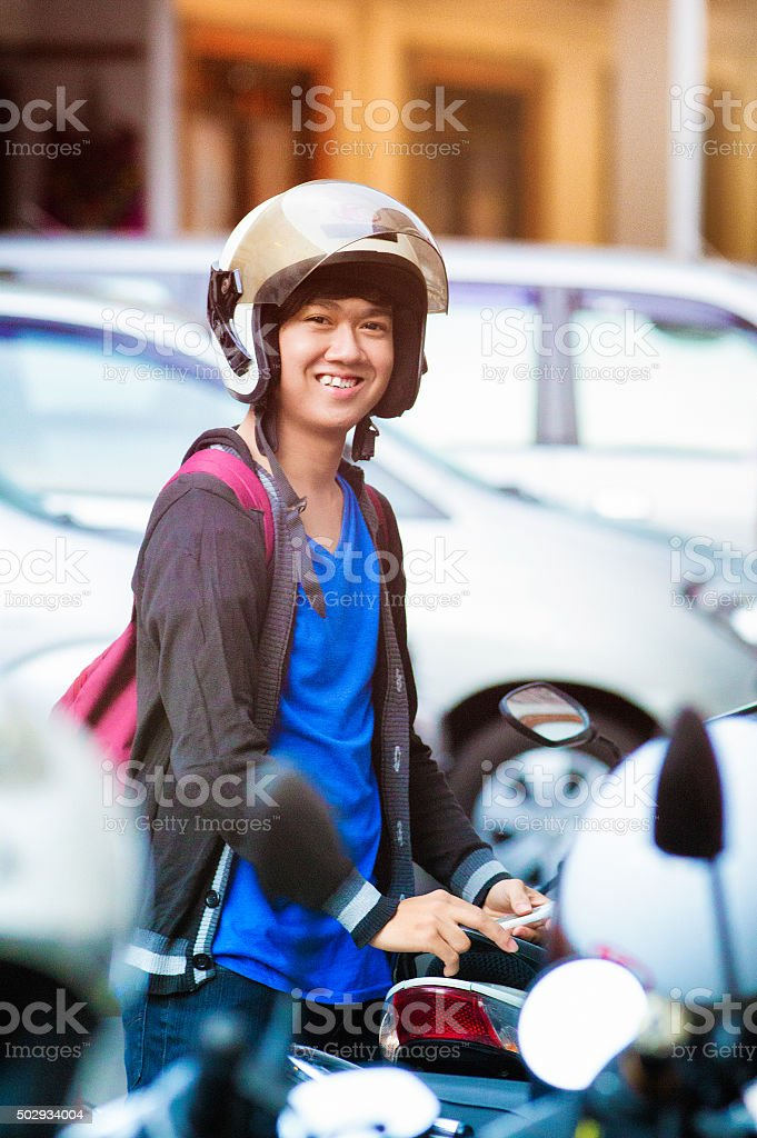 Smiling male Indonesian teenager portrait at parking with helmet stock photo