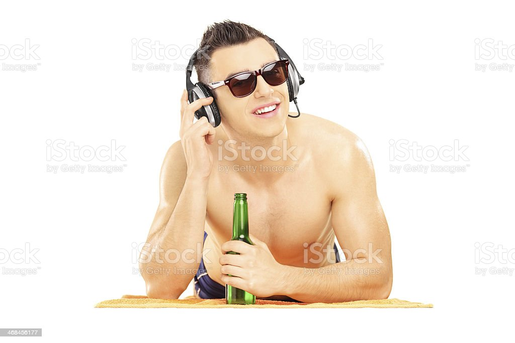 Smiling male on a towel listening music and drinking beer royalty-free stock photo