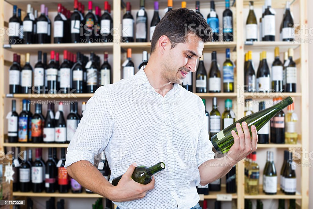 Smiling male professional wine expert holding wine bottles stock photo