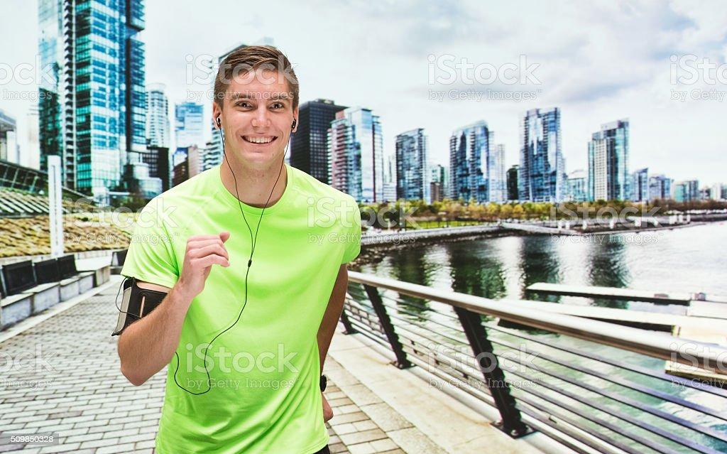 Smiling male runner running outdoors stock photo