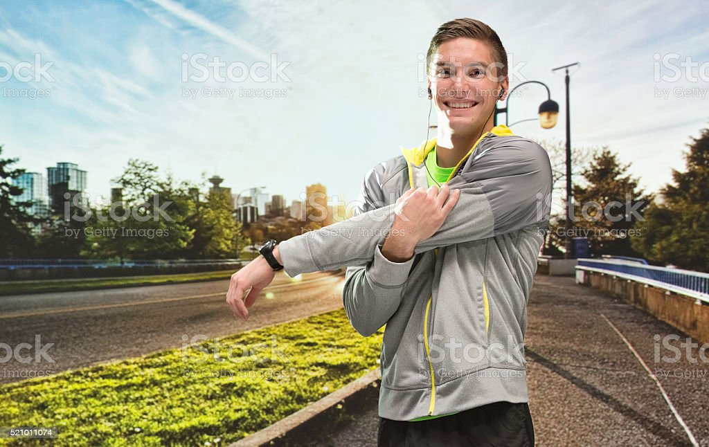 Smiling male runner stretching outdoor stock photo