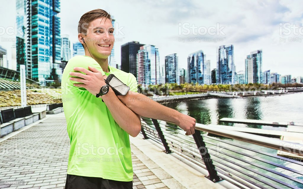 Smiling male runner stretching outdoors stock photo