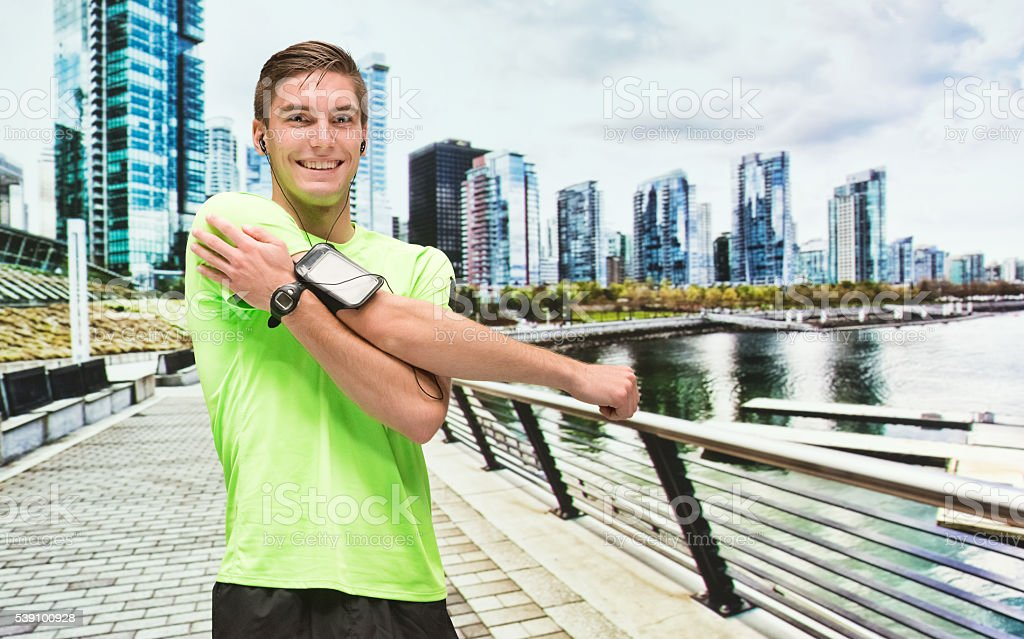 Smiling male runner stretching stock photo