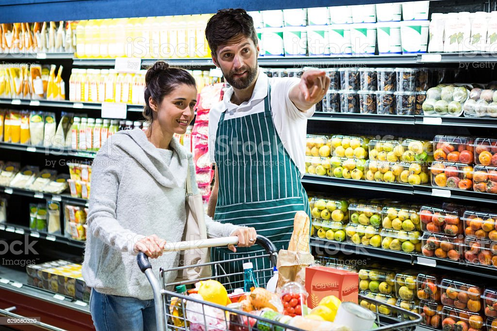 Smiling male staff assisting a woman in organic section stock photo