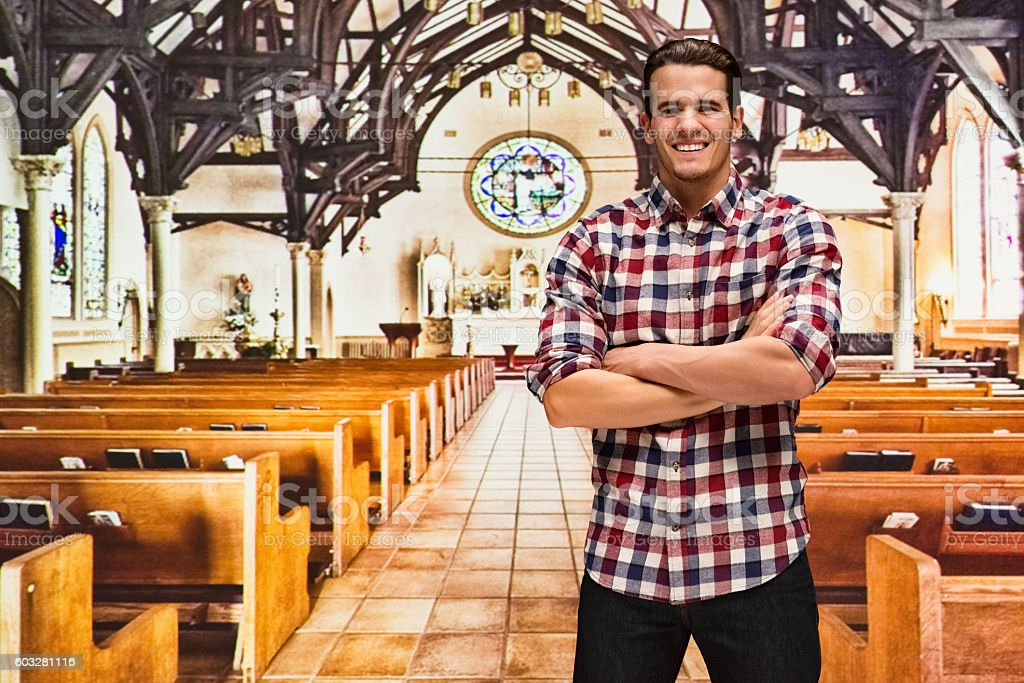 Smiling male standing in church stock photo
