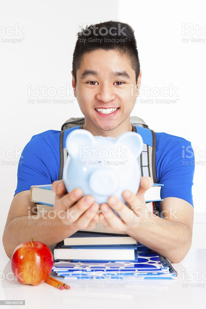 Smiling male student holding piggy bank royalty-free stock photo