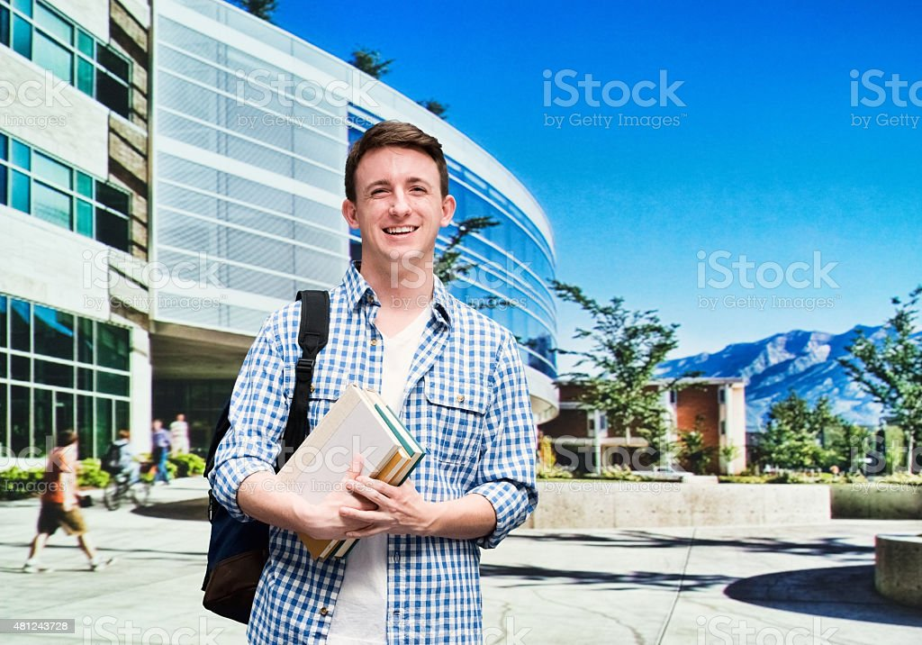 Smiling male student in university campus stock photo