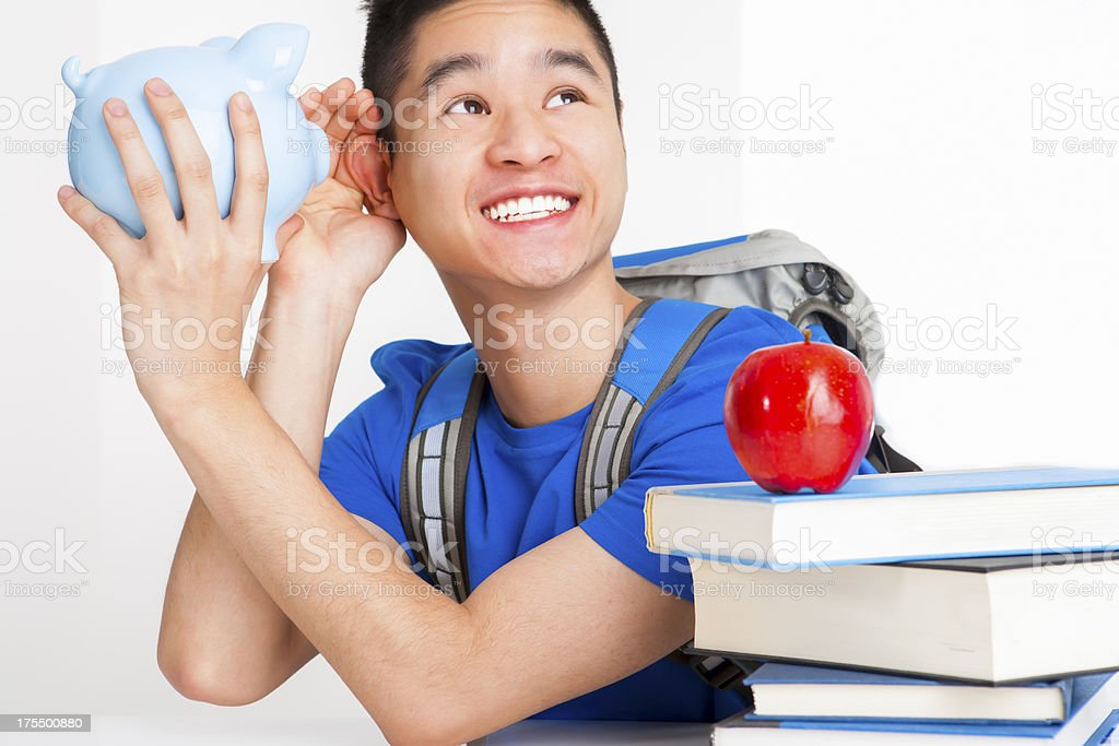 Smiling male student listening to piggy bank royalty-free stock photo
