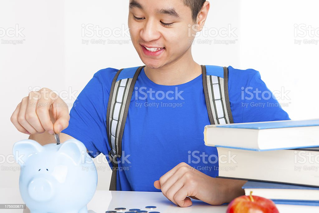 Smiling male student putting money in piggy bank royalty-free stock photo