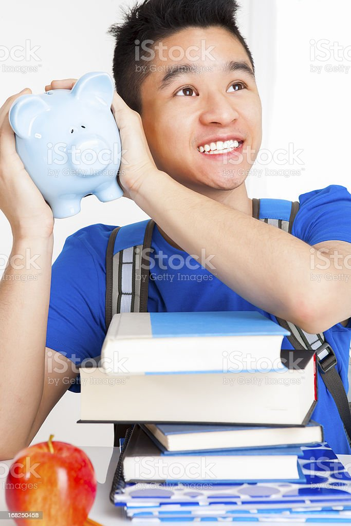 Smiling male student shaking piggy bank royalty-free stock photo