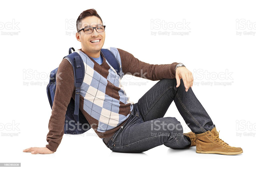 Smiling male student sitting on the floor royalty-free stock photo