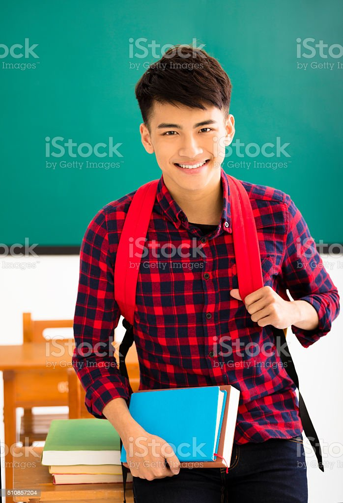 Smiling male student standing in  classroom stock photo