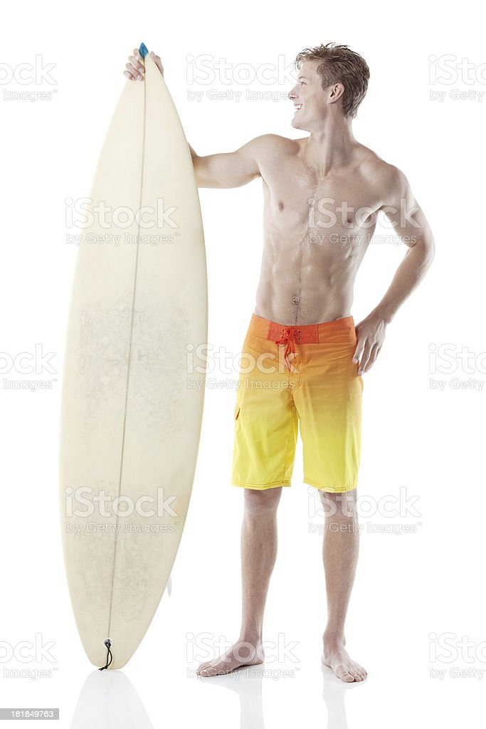 Smiling male surfer standing with a surfboard royalty-free stock photo