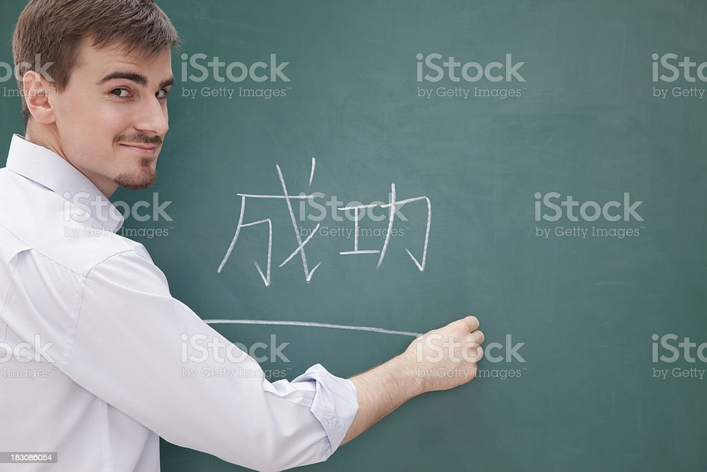 Smiling male teacher in front of chalkboard writing, Chinese characters stock photo