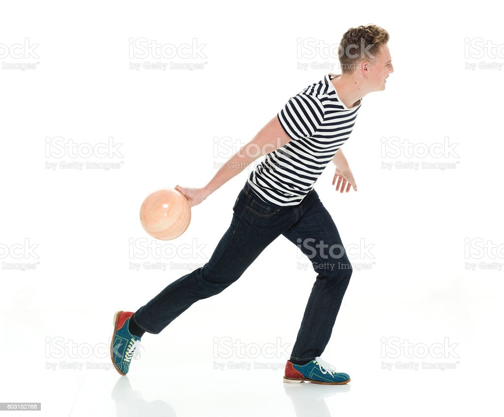 Smiling male throwing bowling ball stock photo