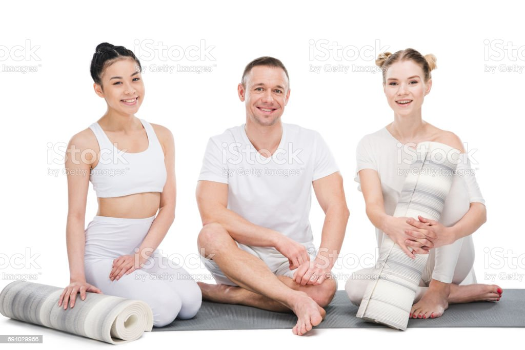 Smiling man and beautiful young women sitting together with yoga mats isolated on white stock photo