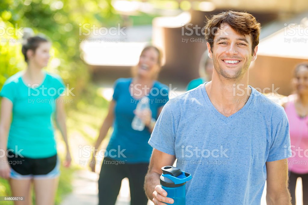 Smiling man and joyful people working out at a park stock photo