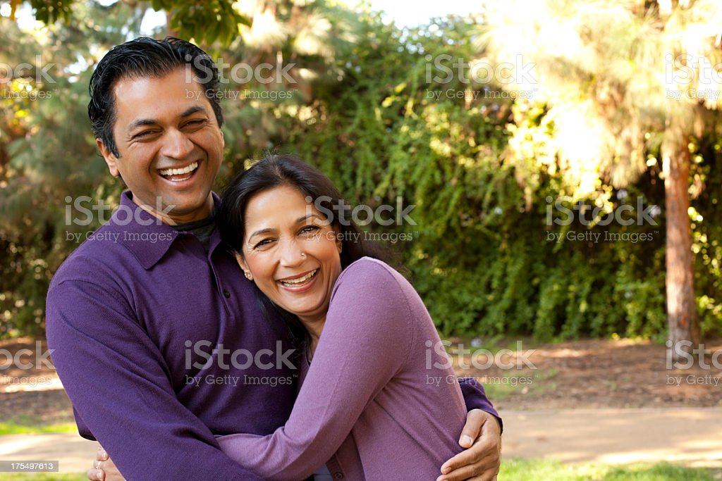 Smiling man and woman, both wearing purple, hugging outside stock photo