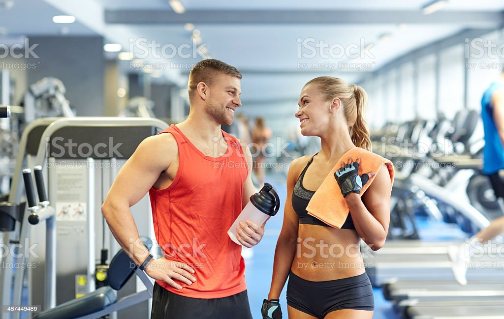 smiling man and woman talking in gym stock photo