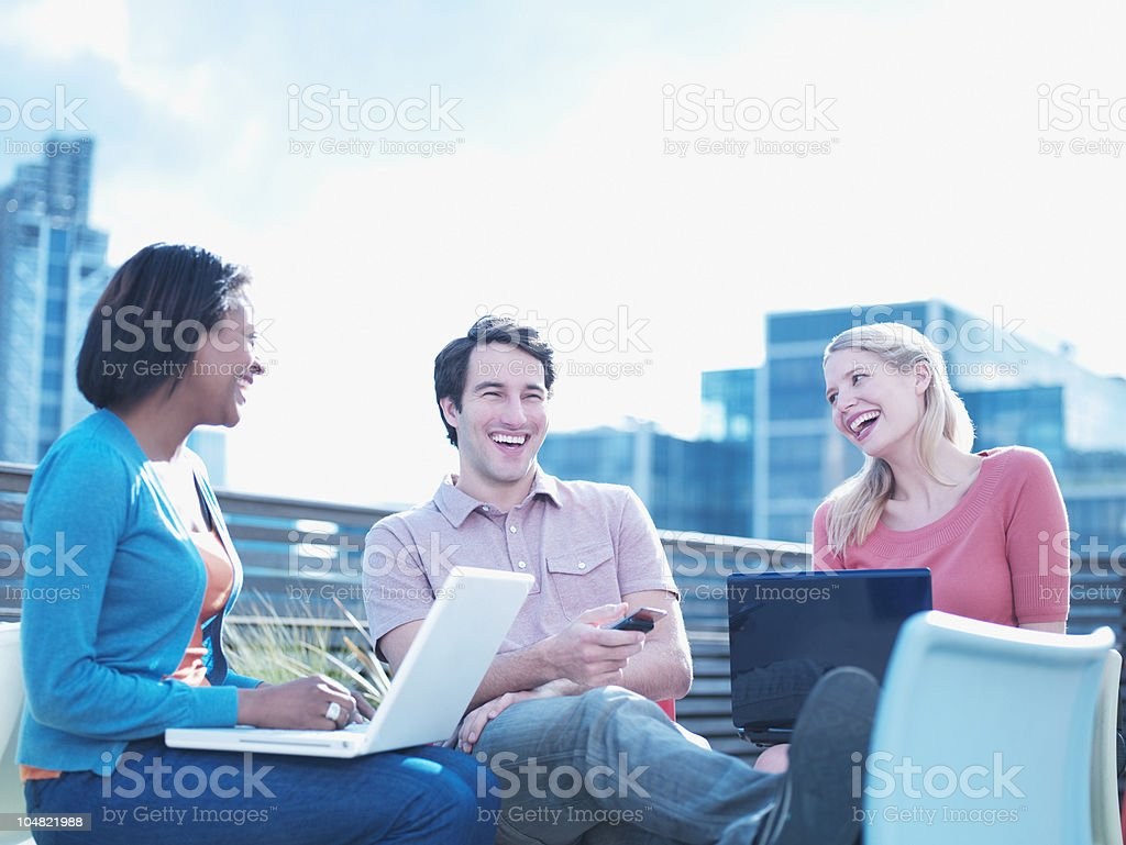 Smiling man and women using laptops on urban balcony stock photo