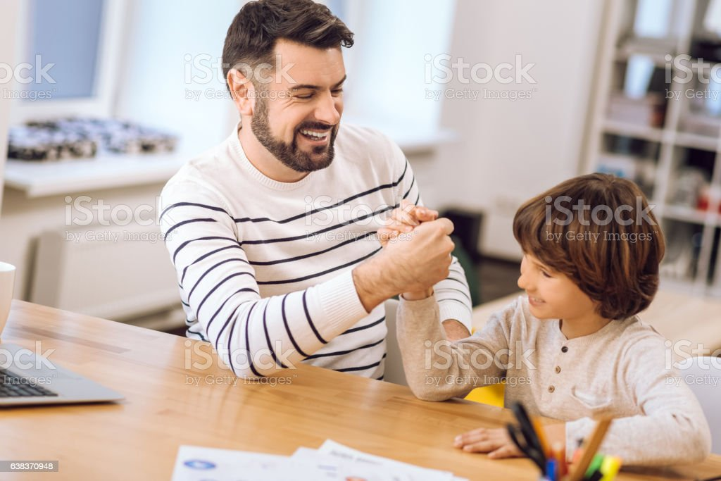 Smiling man arm-wrestling with his son stock photo
