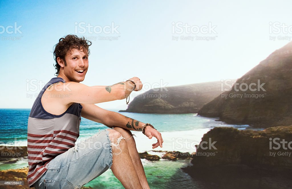 Smiling man at beach and pointing away stock photo