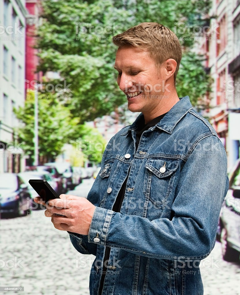 Smiling man at street and using mobile stock photo