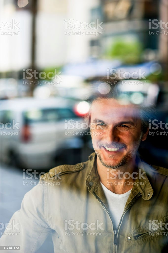 Smiling man behind glass reflecting a street full of cars stock photo