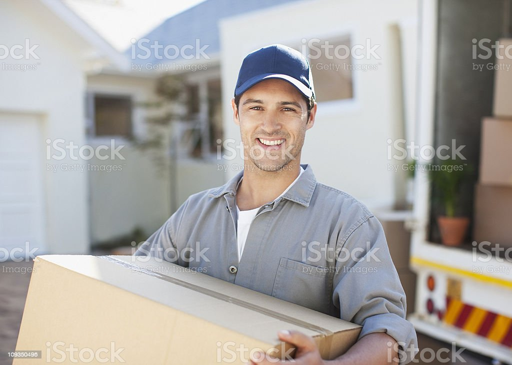 Smiling man carrying box from moving van stock photo