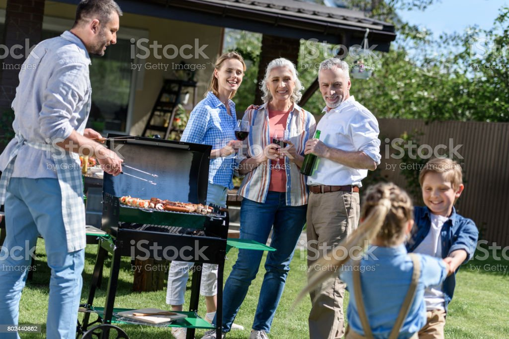 smiling man cooking food on barbecue with family enjoying weekend near by stock photo