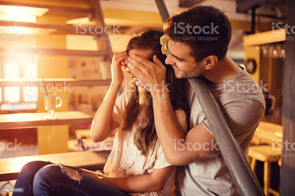 Smiling man covering girlfriend's eyes and surprising her. stock photo